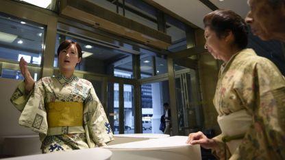 Хуманоиден робот (вляво) посреща клиенти в универсален магазин в Токио.