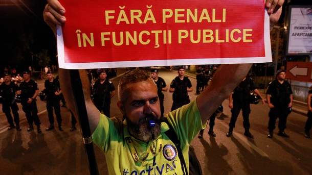 """Мъж държи плакат с надпис """"Без наказания за чиновници"""" на протеста снощи в Букурещ."""