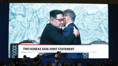Журналисти гледат на голям екран как Ким Чен-ун и Мун Дже-ин се прегръщат след подписване на общата декларация.
