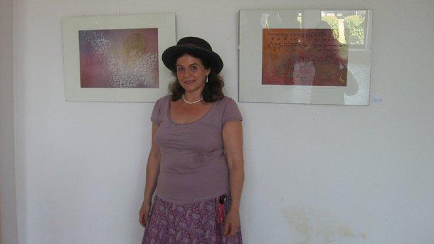 """Художничката Антония Дуенде пред картини от изложбата си """"Глаголически следи"""" в Центъра за култура """"Глигор Пърличев"""" в Охрид."""
